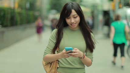 Young Asian Woman in city texting cellphone