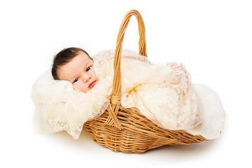 Newborn baby smiling in a wicker basket