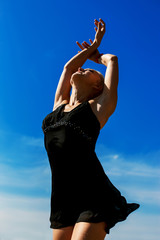 Beautiful young dancer performing yoga-dance outdoors with blue