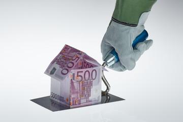Arbeite Handschuh baut Haus aus 500 Euro Schein