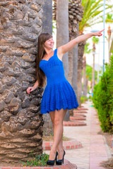 young girl in a blue dress is pointing in the direction