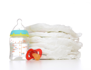 stack of diapers nipple soother and baby feeding bottle with wat