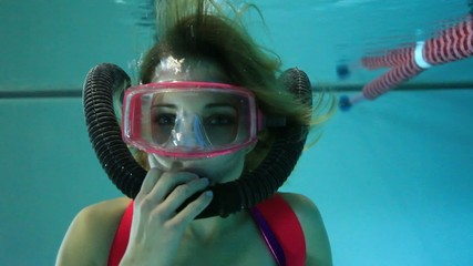 Female scuba diver playing with regulator