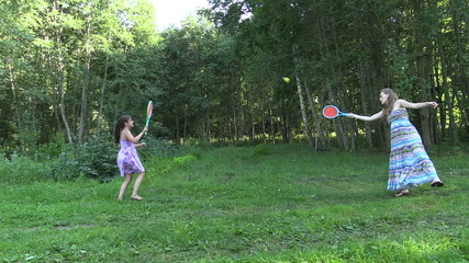 Active pregnant woman with girl play badminton game in park