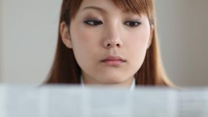 新聞を読み正面を見据える女の子