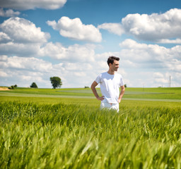 Man standing in a field of young wheat