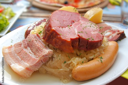 Plate of ham and sausage served with sauerkraut