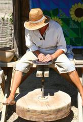 Гончар работает на гончарном круге.