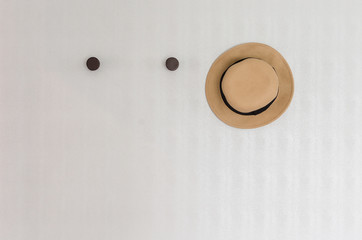 brown hat hanging on wall hook