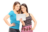 Two teenage girls looking at a tablet