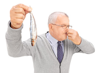 Senior gentleman holding a rotten fish