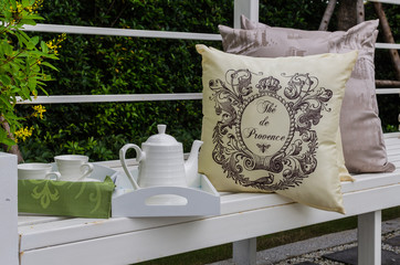 tray of white tea set with pillows on bench