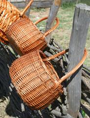 Плетенные корзины висят на плетне.