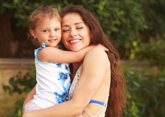 Beautiful young mother hugging her small kid girl with smile
