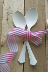 vintage white spoons, pink ribbon on wooden background