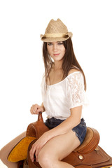 brunette cowgirl sit on saddle look slight smile