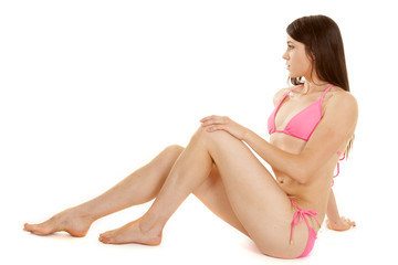brunette woman pink bikini sit look to side