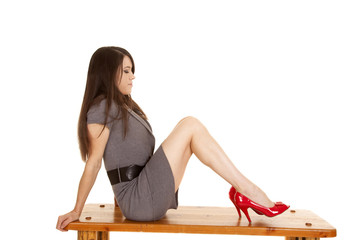 woman gray dress red shoes sit side