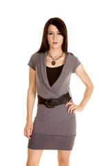 woman in a gray dress serious hand on hip