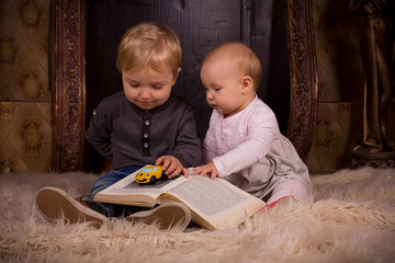 children on a fluffy carpet with book