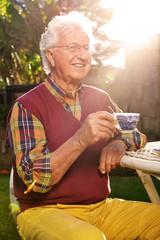 Anziano con tazza al tramonto
