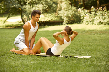 Fitness Exercise. Young couple training in Summer Park