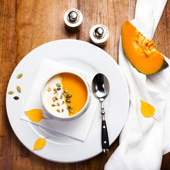 Pumpkin soup with cream and pumpkin seeds on a white plate on wo