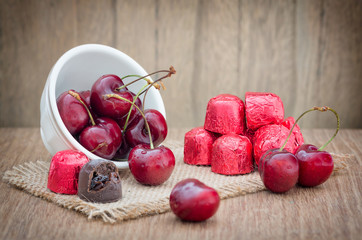 Cherries and cherry chocolate on wooden table