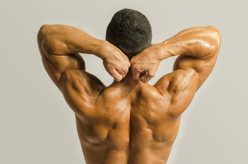 Bodybuilder showing his back,shoulders, triceps and biceps