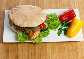Pita bread with grilled chicken breast with lettuce and paprika