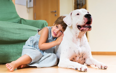 Little girl hugging white dog