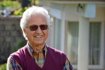 Uomo anziano sorridente in giardino