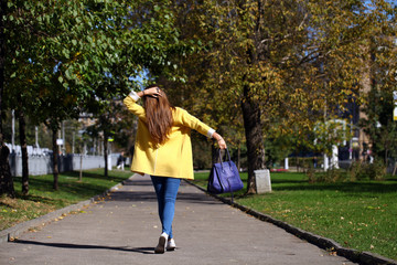 Happy woman in yellow coat walking autumn street