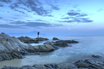 Fisherman on the rocks at dusk