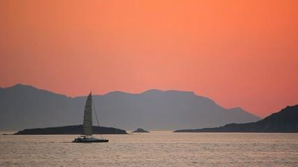 Sailboat near islands in sunset