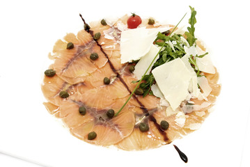 Slices of salmon with herbs and cheese on a white plate
