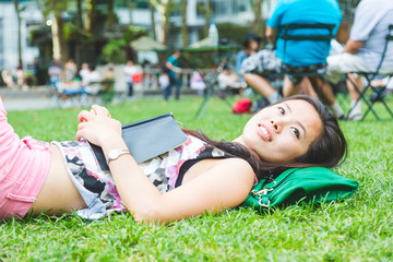 Asian Girl Laying Down on the Grass at Park