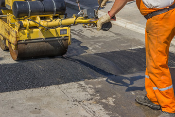 Worker installing asphalt speed bump