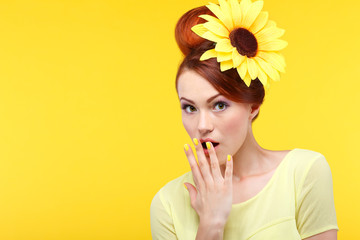 Beautiful girl on a yellow  with yellow flower in hairs