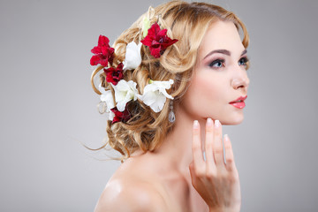 Beautiful girl on a grey with varicoloured flowers  in hairs