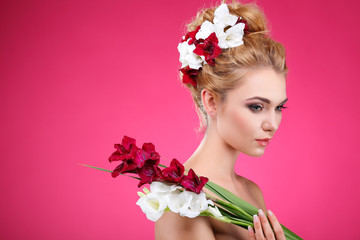Beautiful girl on a pink with varicoloured flowers in hairs,