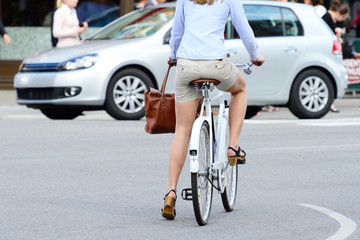 Woman on bike waiting, car in background