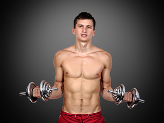 Sexy muscular man lifting dumbbells