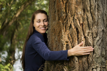 Pretty woman hugging a tree