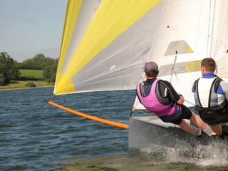 two people sailing a small grey dinghy on a lake