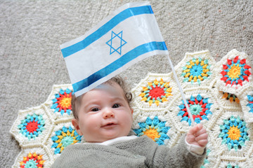 Israeli newborn baby holding the Israeli flag.