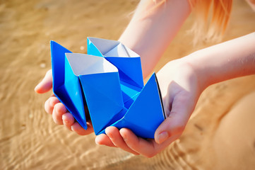 Closeup photo of paper ship in children hand