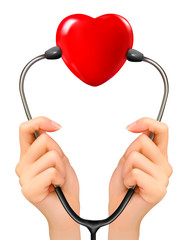 Medical background with hands holding a stethoscope with red hea