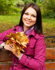 Young elegant woman with autumn leaves