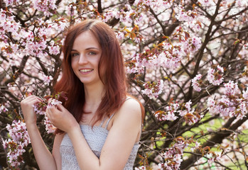 young woman in spring flowers garden
